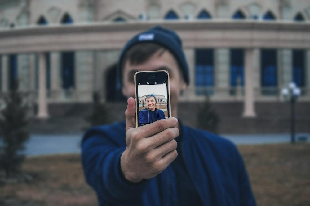 man taking photo near building