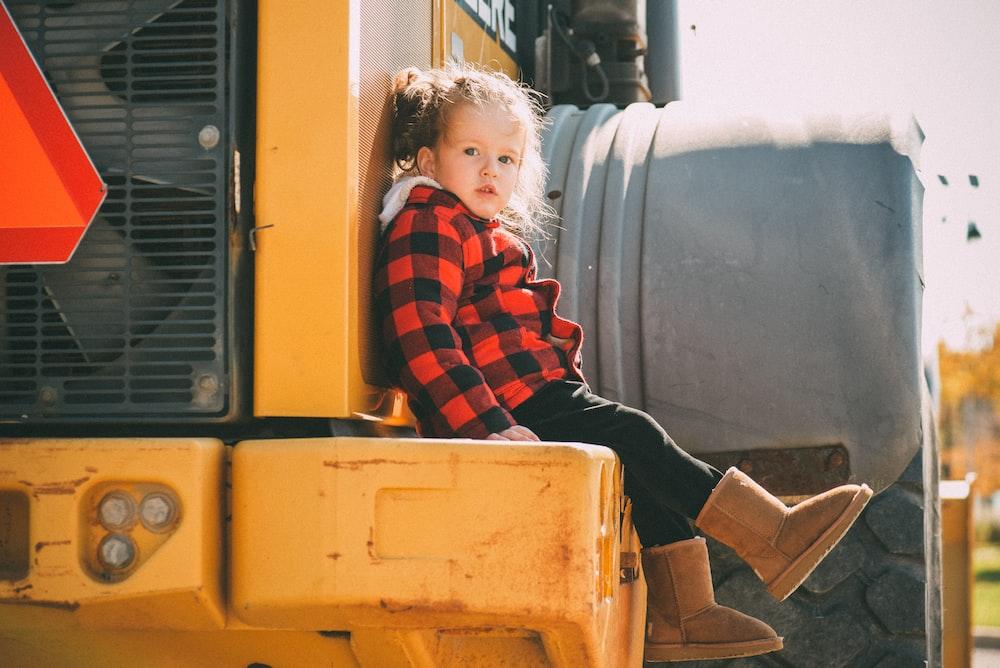 toddler girl sitting on yellow heavy equipment