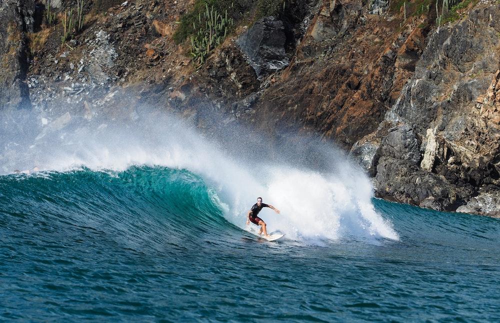 man surfboarding near rock mountain