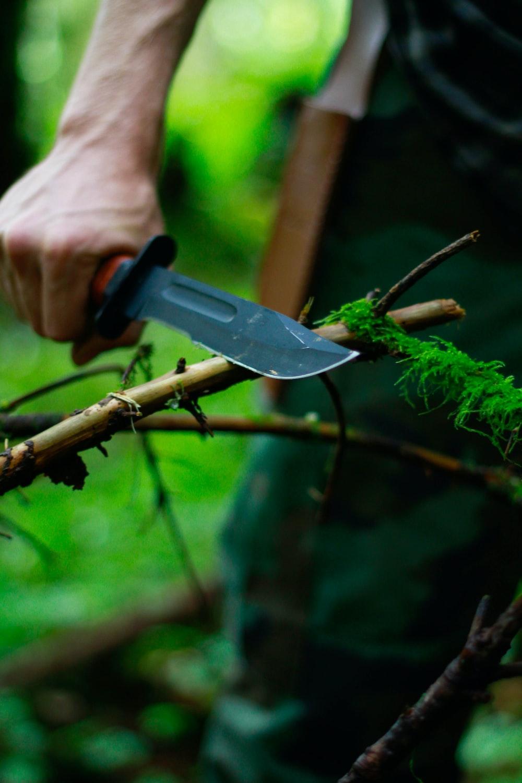 man holding hunting knife near twig