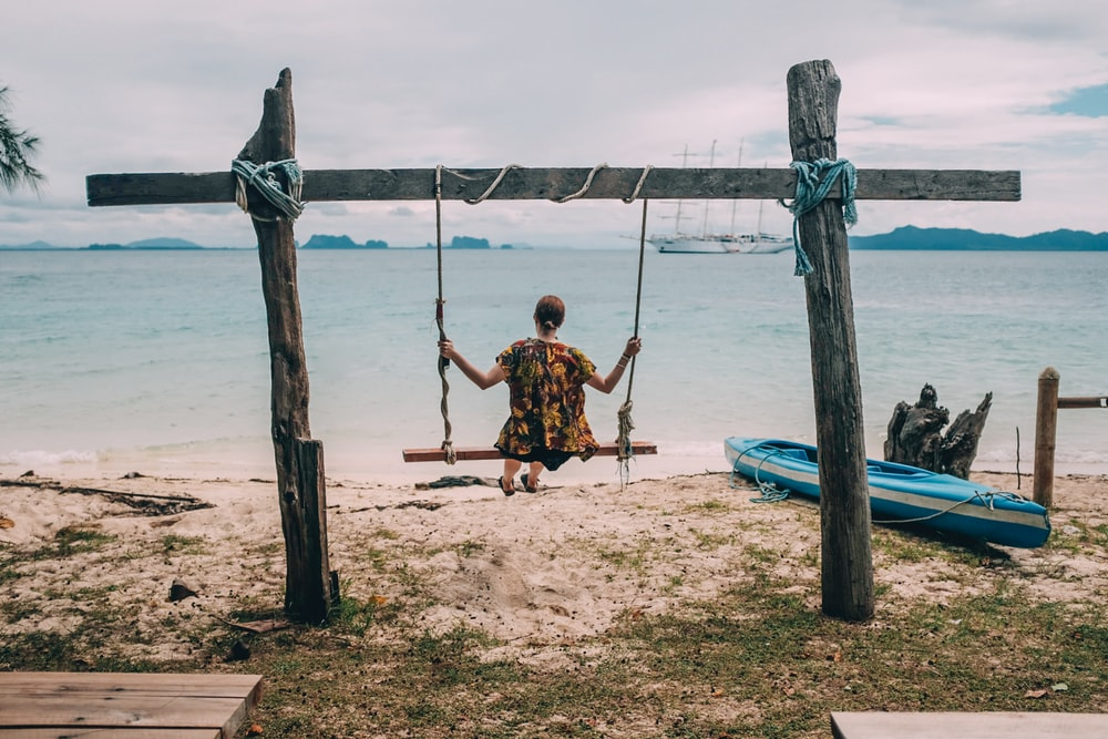 woman sitting on swing facing the ocean during day