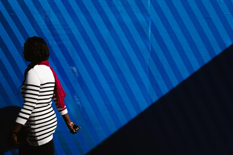 woman walking near blue wall