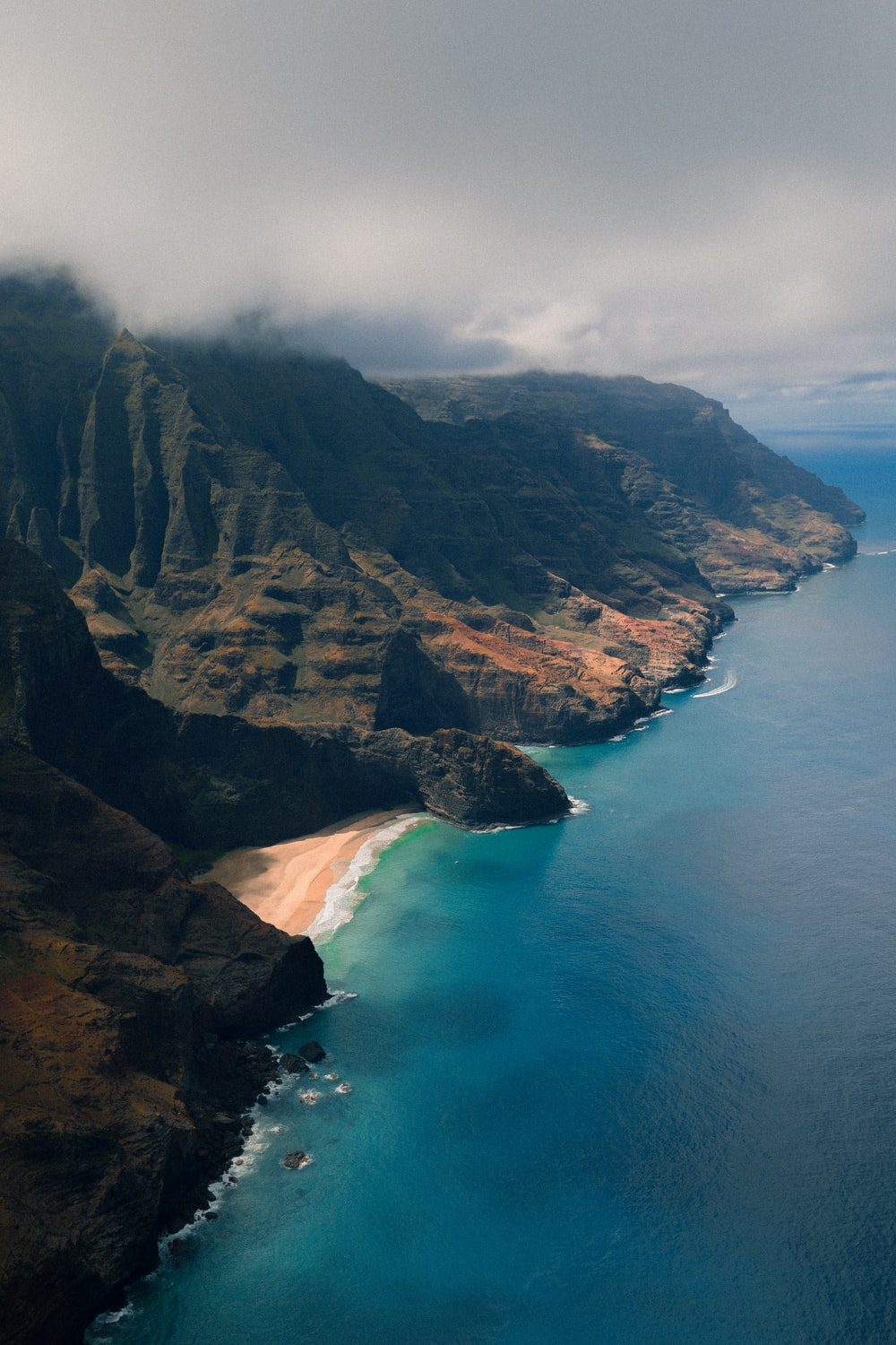 aerial photography of island under cloudy sky