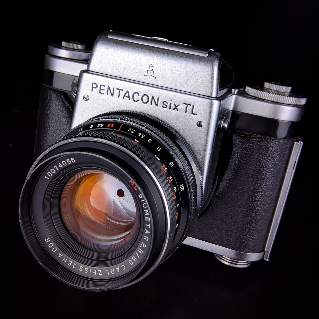 A Pentacon Six TL film camera with a Zeiss Biometar 80mm f/2.8 in good condition on a dark Background.