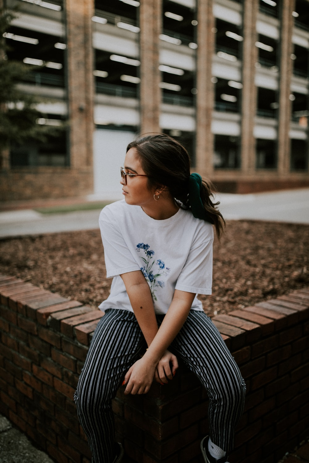 shallow focus photo of woman in white crew-neck T-shirt sitting on concrete bench