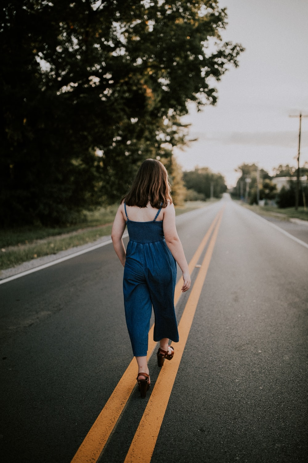 woman walking in the middle of black asphalt road during daytime