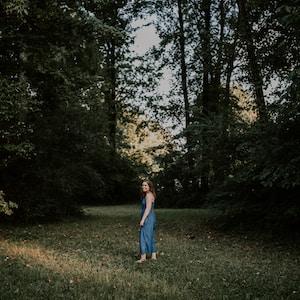 woman standing on grass field between trees