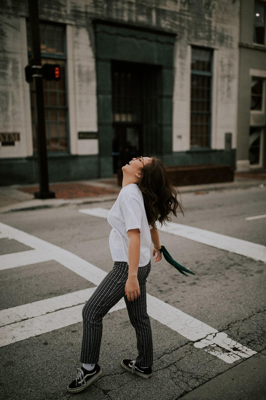 woman standing on road's pedestrian lane