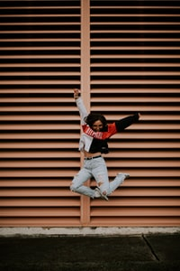 woman jumping in front of brown wall
