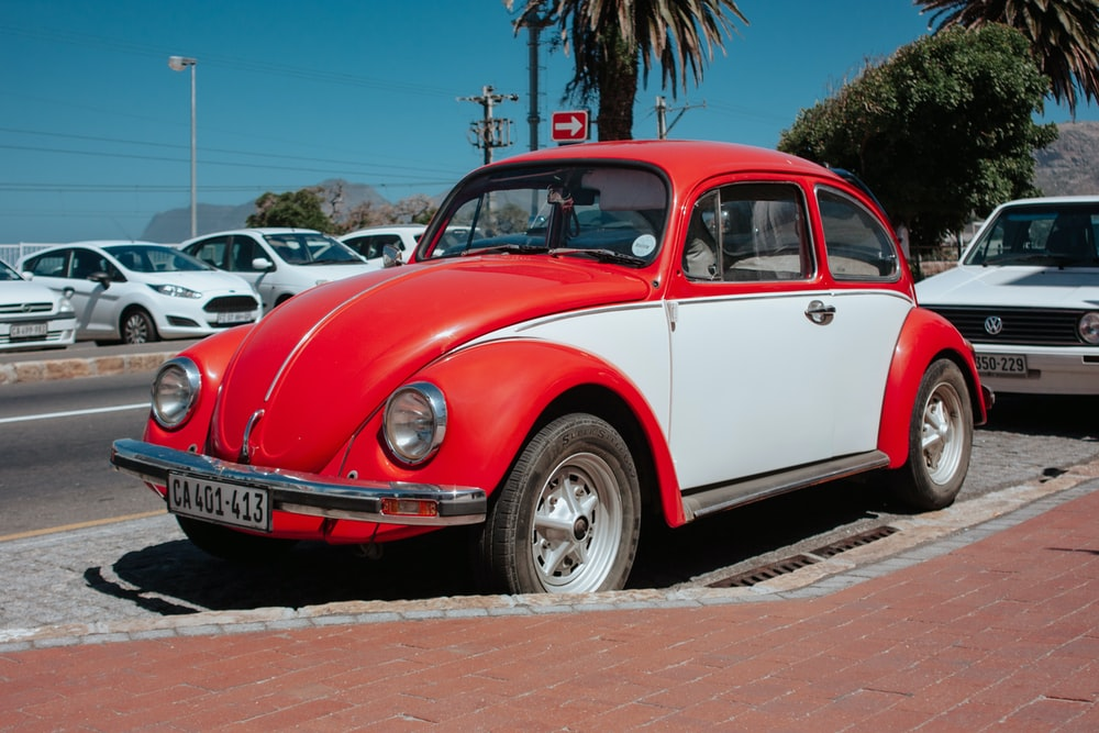 red and white Volkswagen beetle parked on side of road