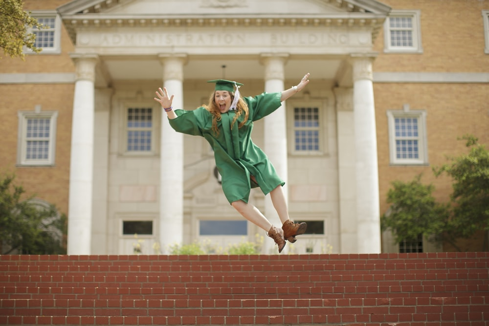 woman wearing mortarboard jumping on staris