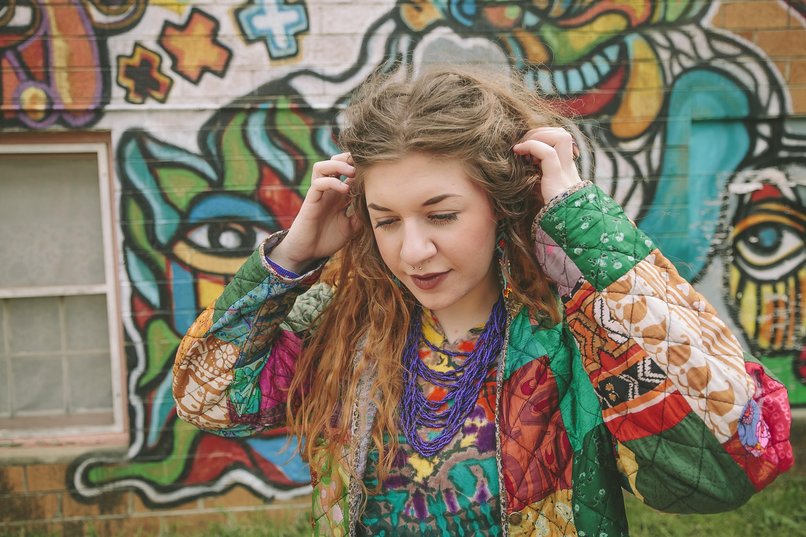 woman standing near wall with graffiti