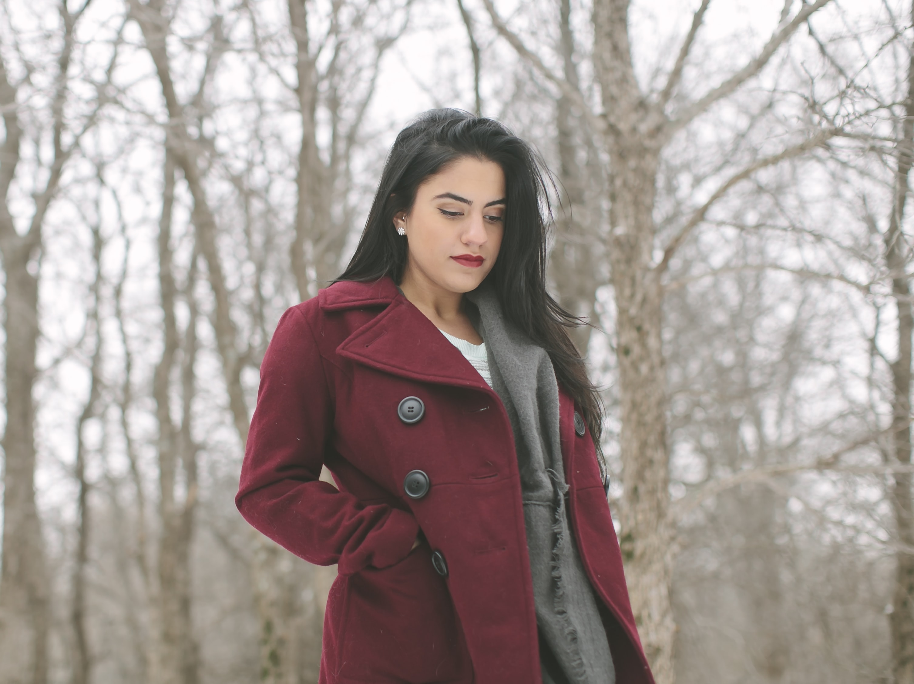 woman wearing red coat looking down