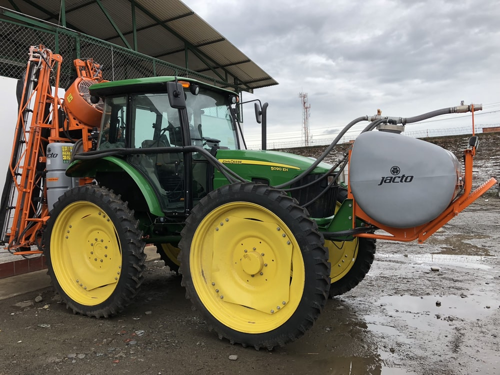 green tractor under gray sky during daytime