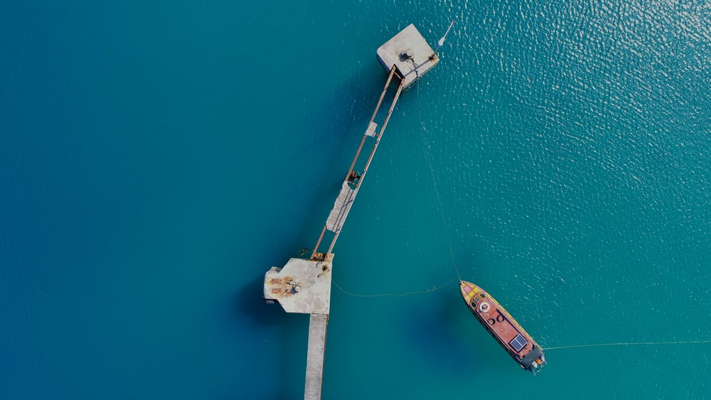 aerial photography of boat approaching bridge