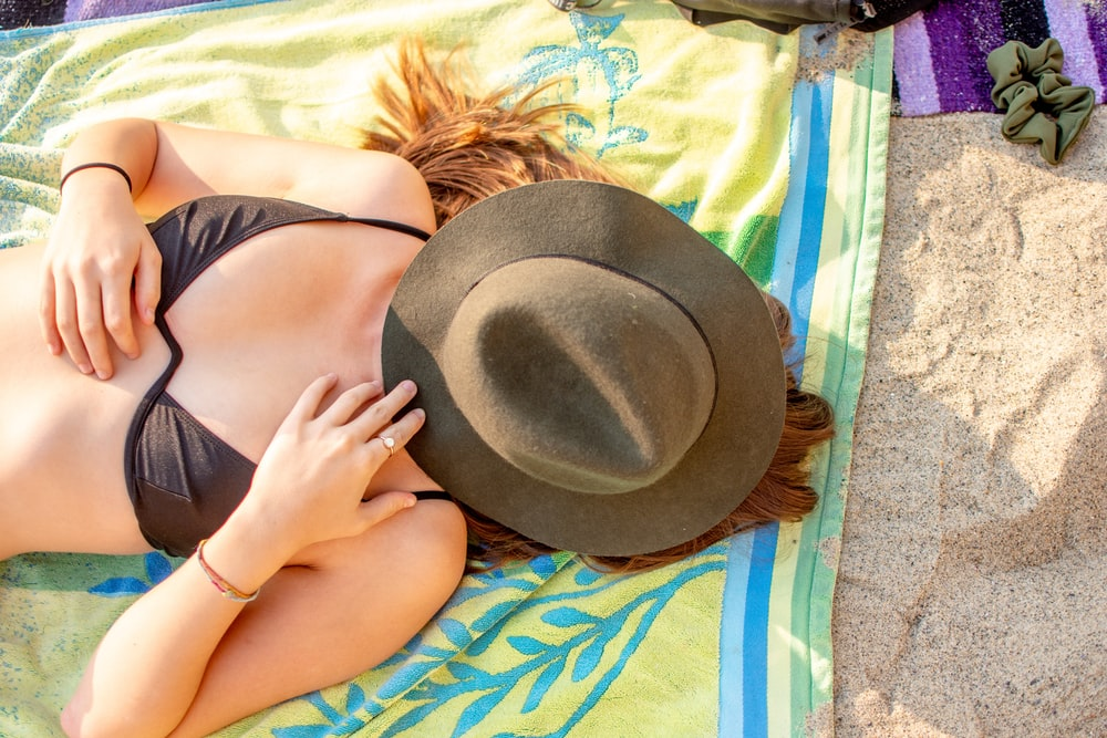 woman laying down with hat covering face