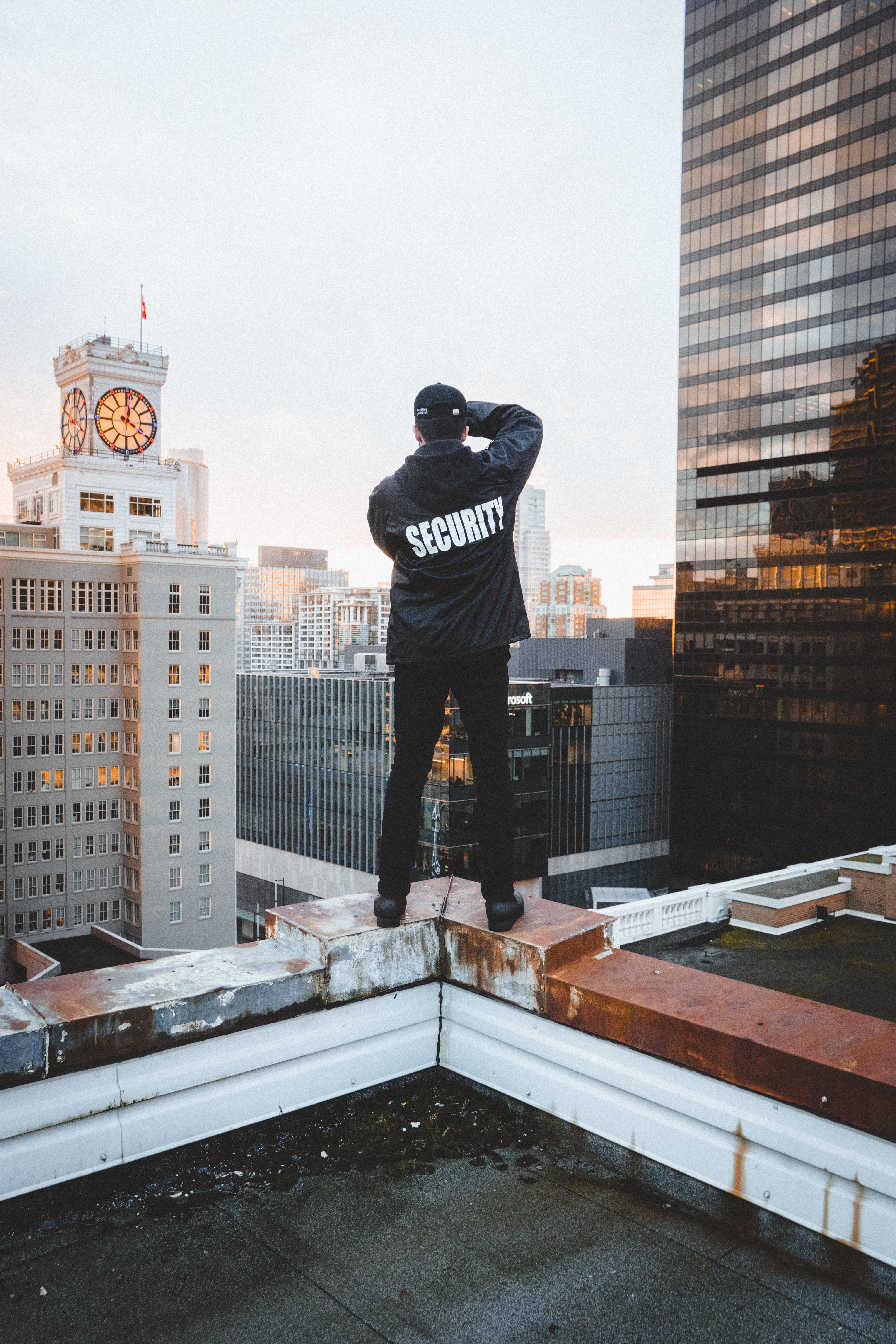 man standing on top of building under white sky during daytime