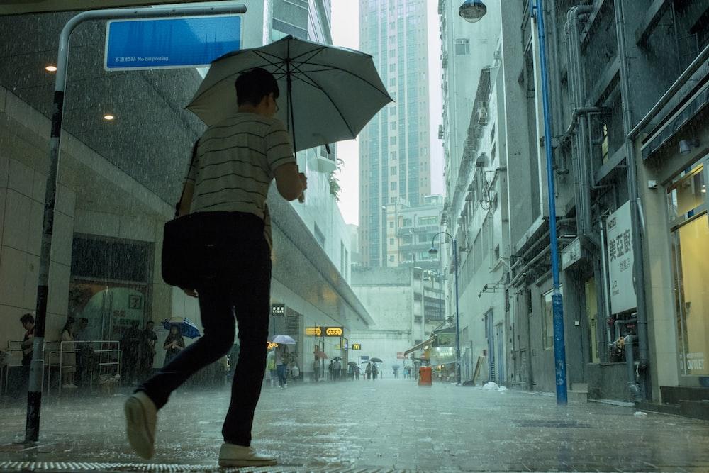 woman walking on street while its raining