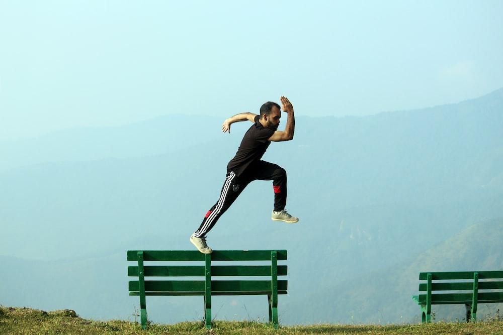 man jumping beside bench