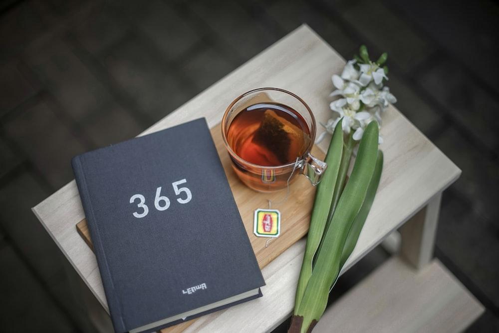 365 book beside clear glass mug
