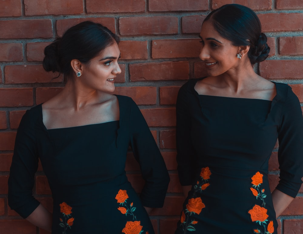 smiling two women wearing black and orange floral dress leaning on brown wall