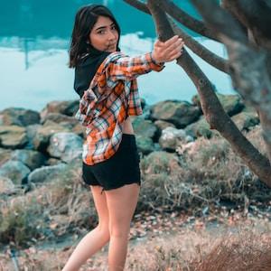 woman wearing orange plaid blouse standing beside tree near body of water