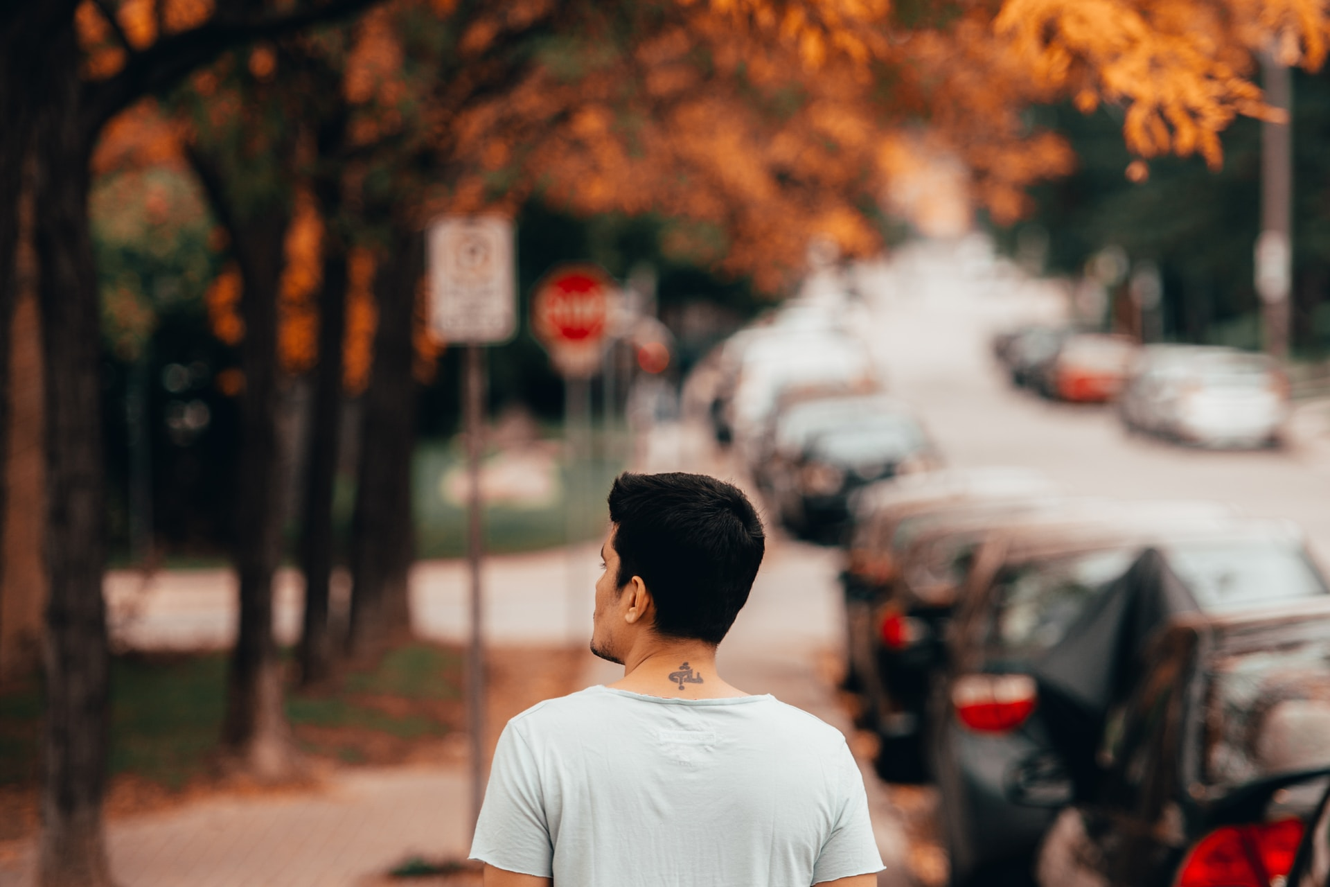 man wearing white shirt walking near vehicles and tree