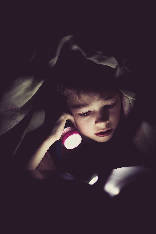 child holding flashlight reading book