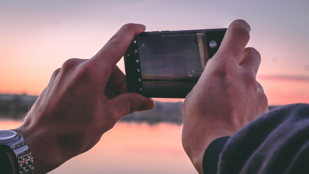 person holding a phone taking a picture of golden hour