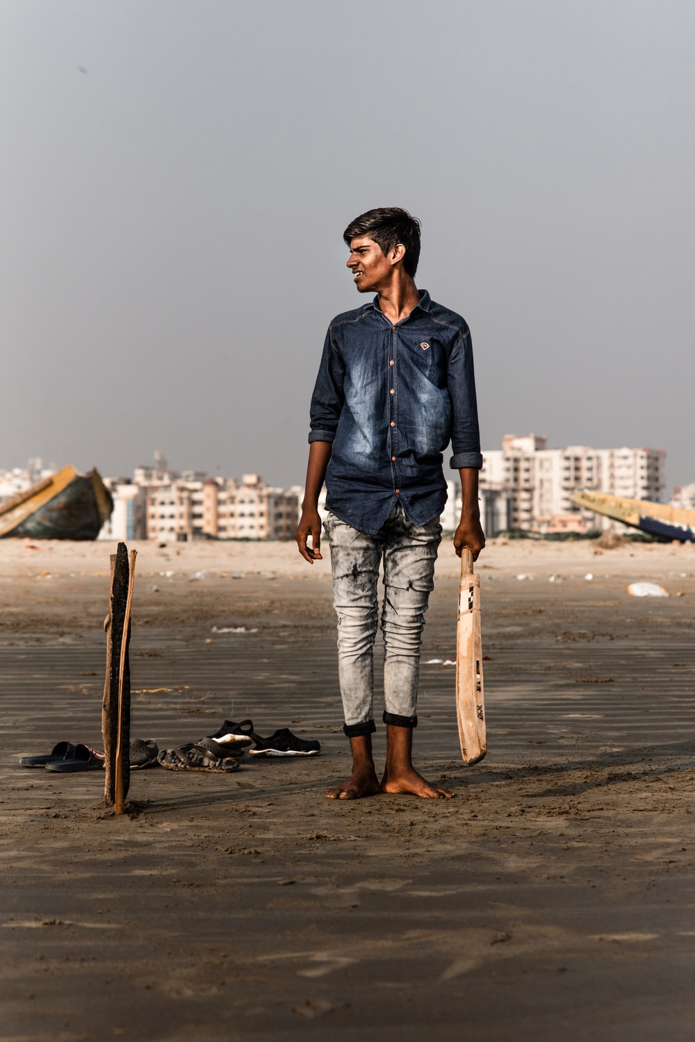 smiling man standing holding cricket bat while looking at right side during daytime