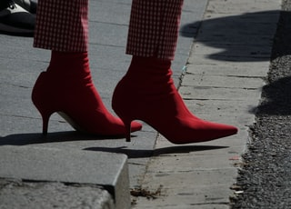 person wearing red shoes standing on road