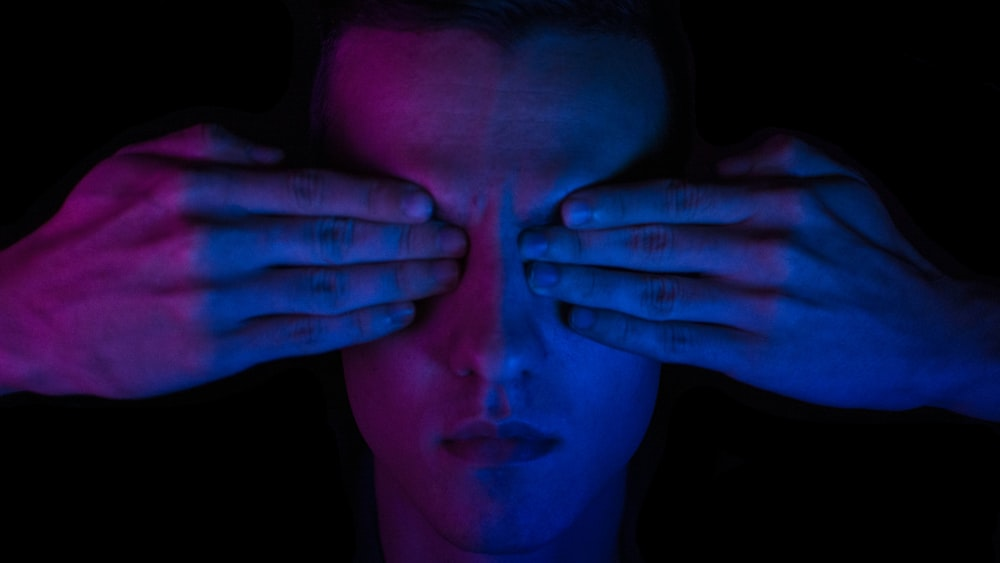 person covering his eyes wallpaper