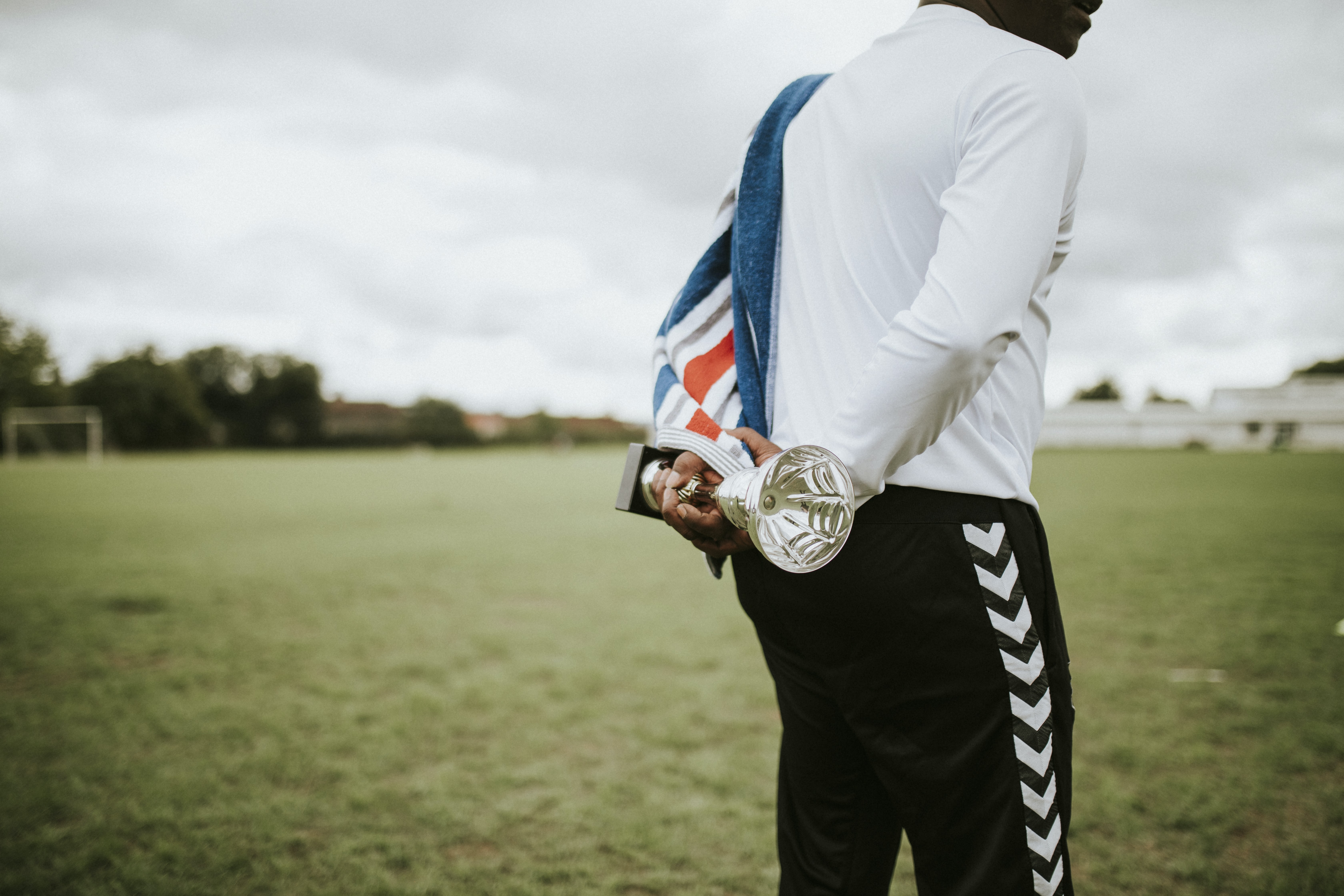 standing man holding silver trophy on green grass open field duirng daytime