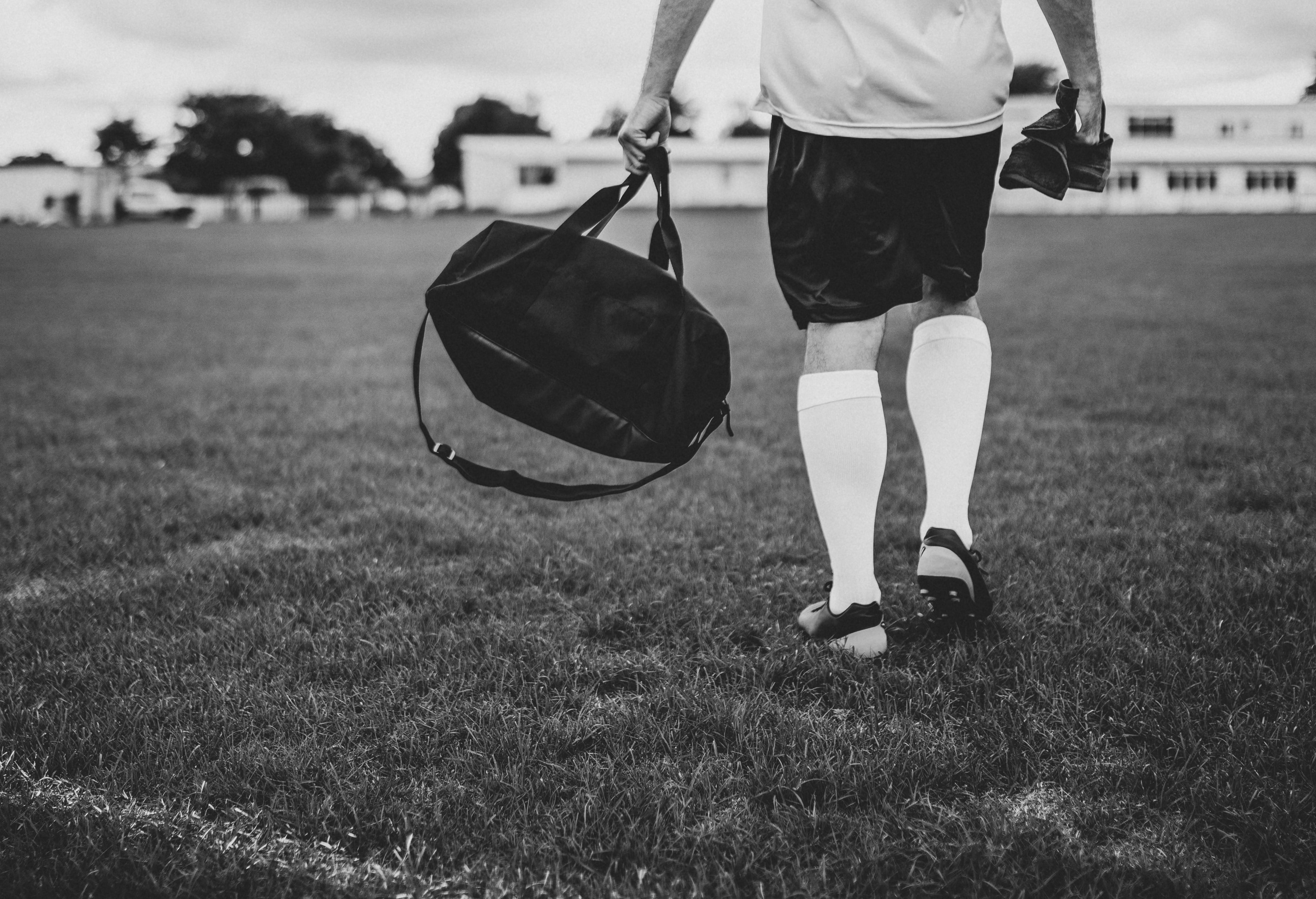 grayscale photography of man holding duffel bag