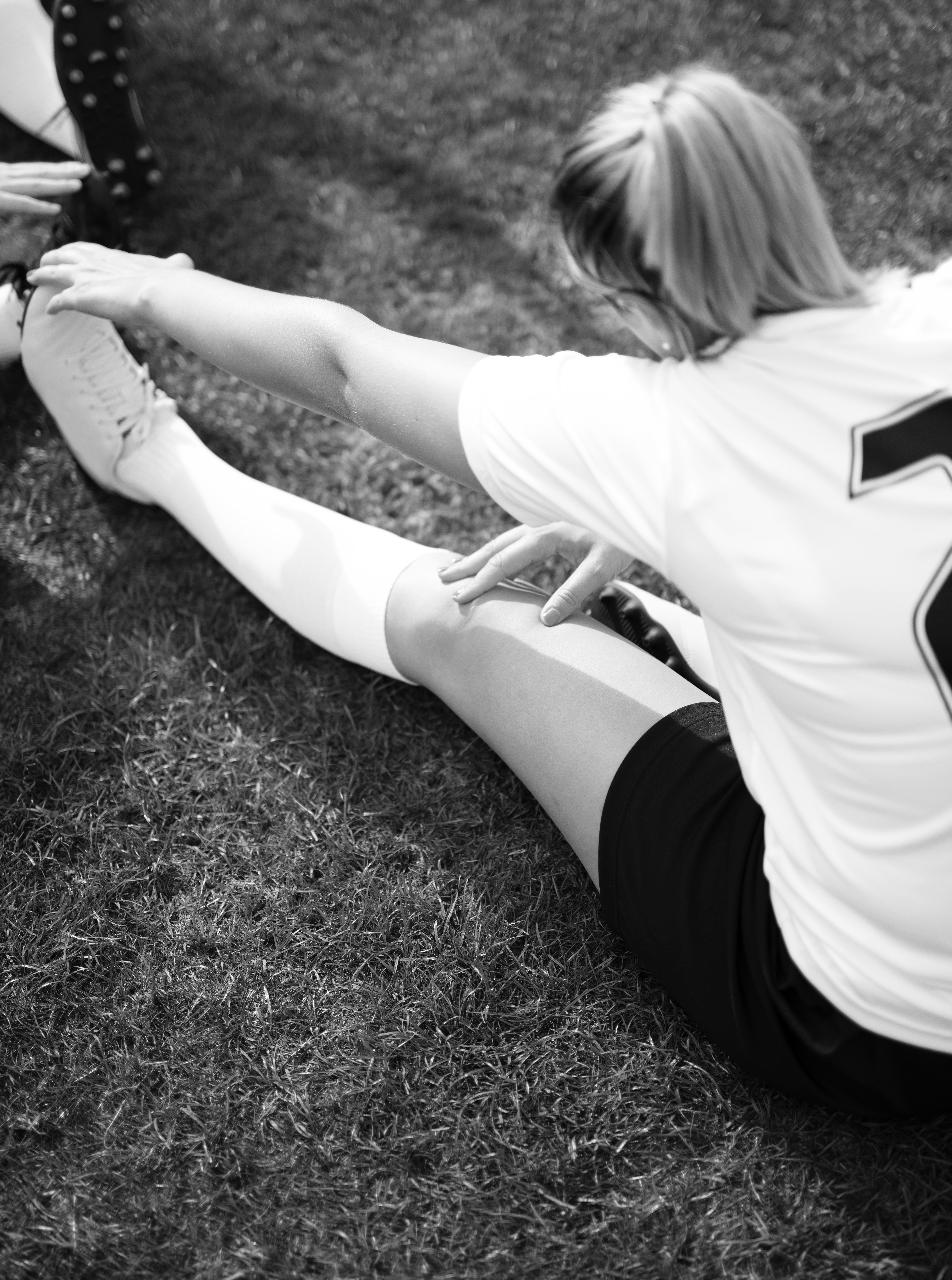 grayscale photography of woman sitting on grass reaching her left foot