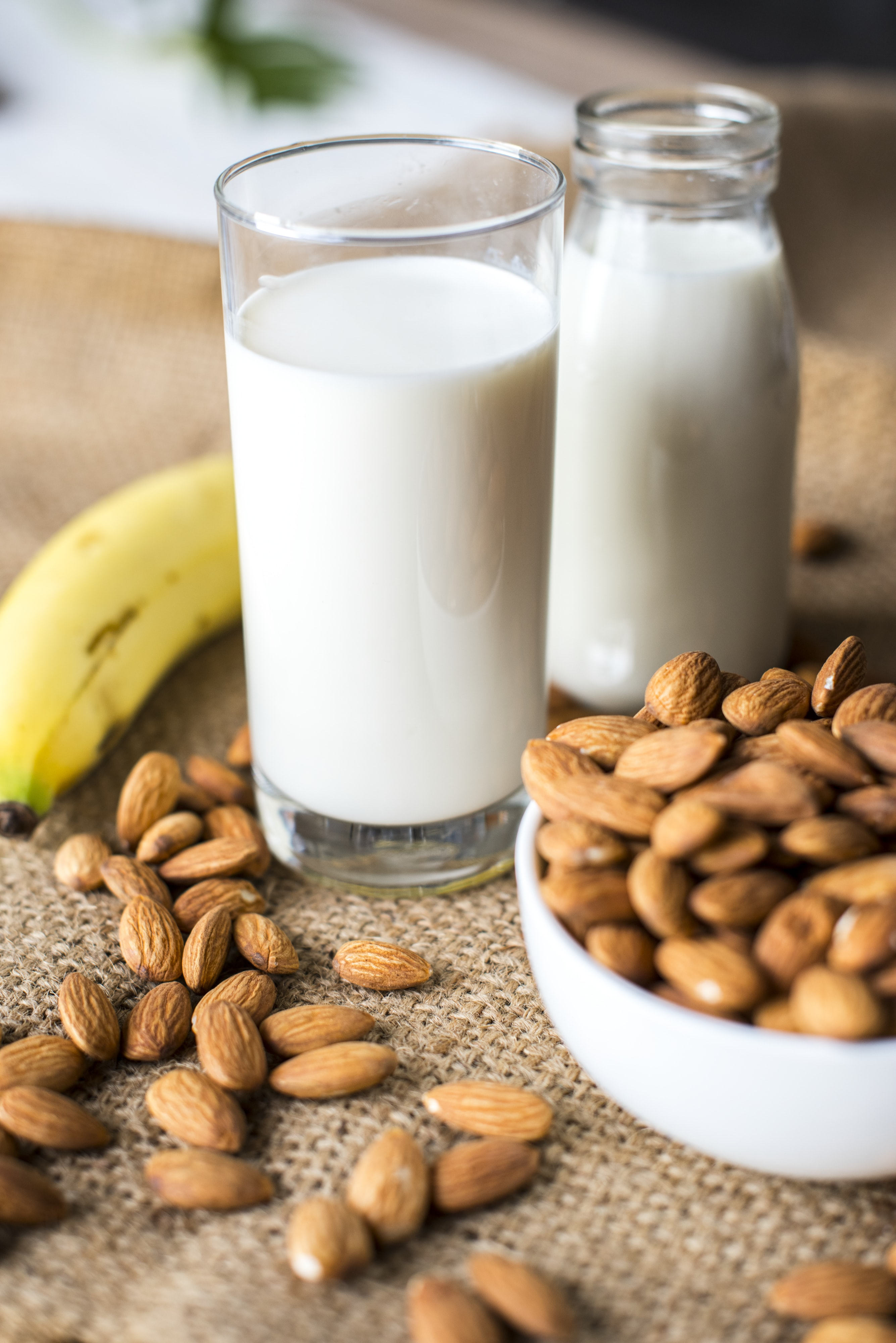 glass of milk beside bowl of nuts