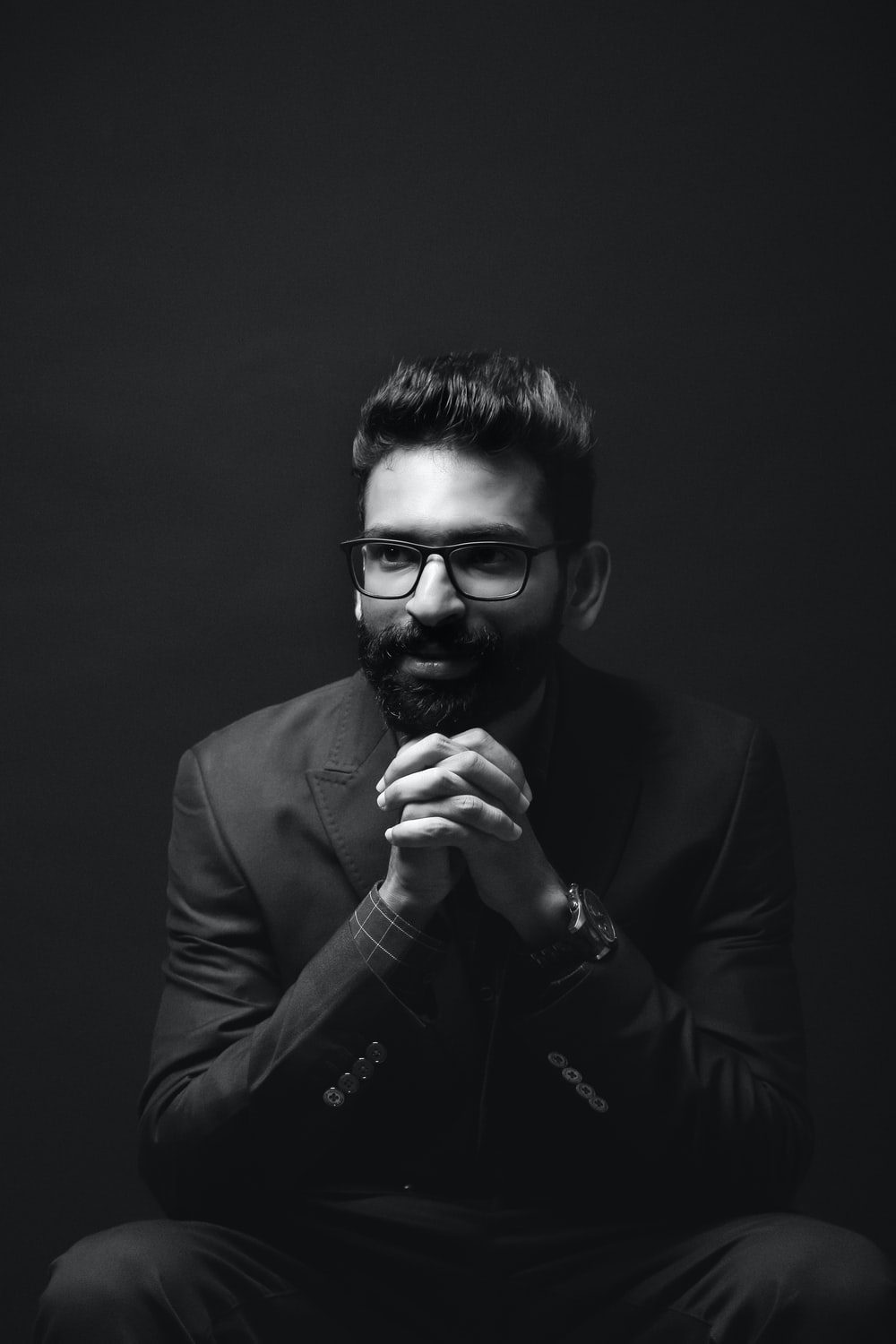 grayscale photography of sitting man wearing suit