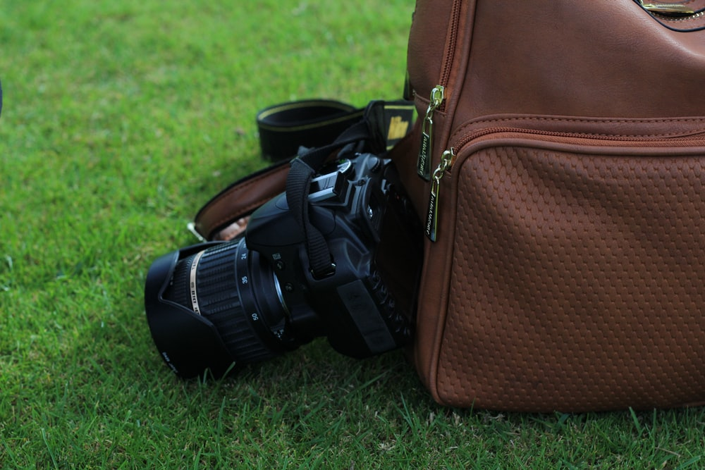 video camera beside brown backpack on green grass