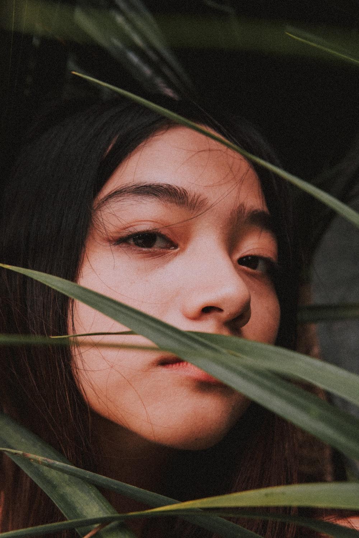 woman behind blades of grass