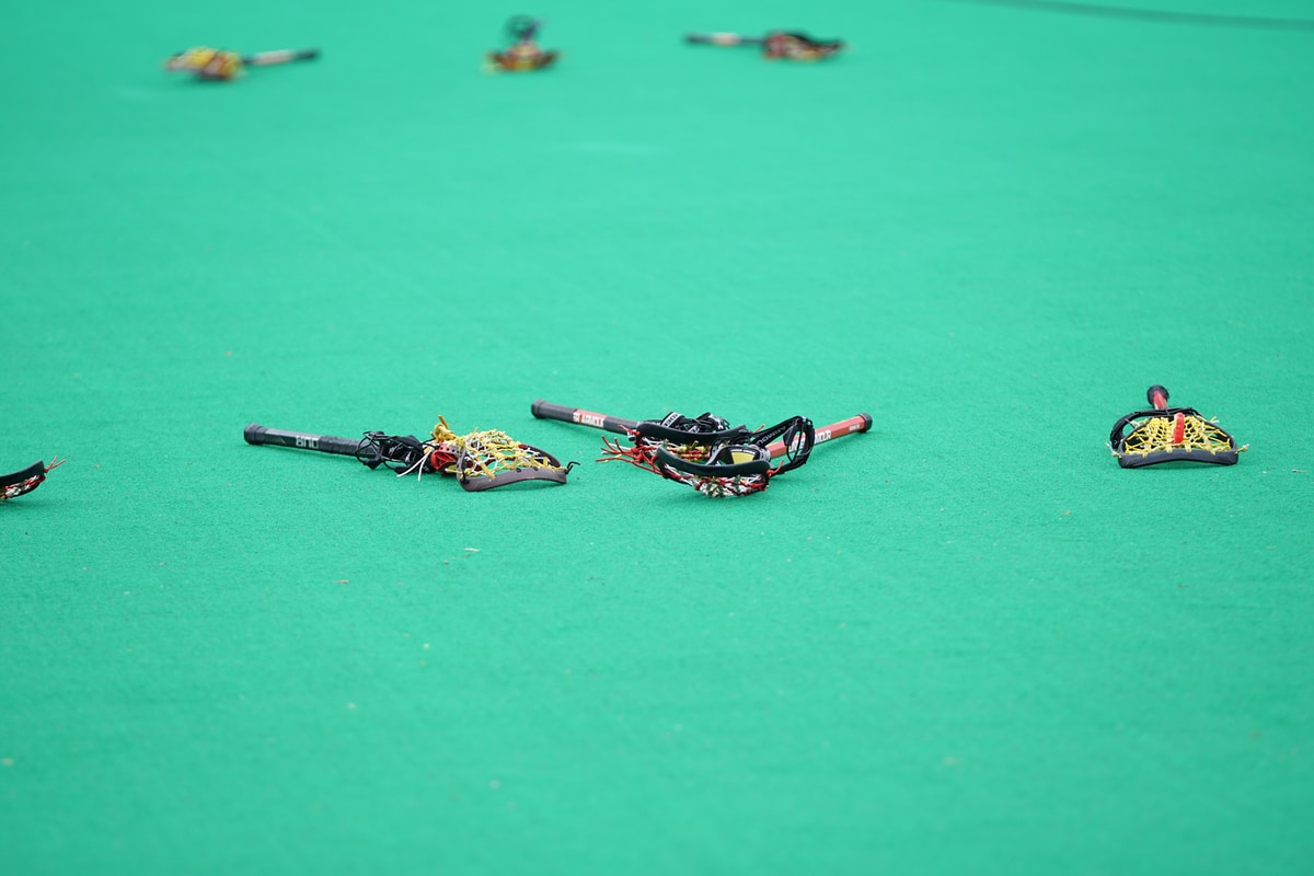 Lacrosse sticks laying on a bare turf