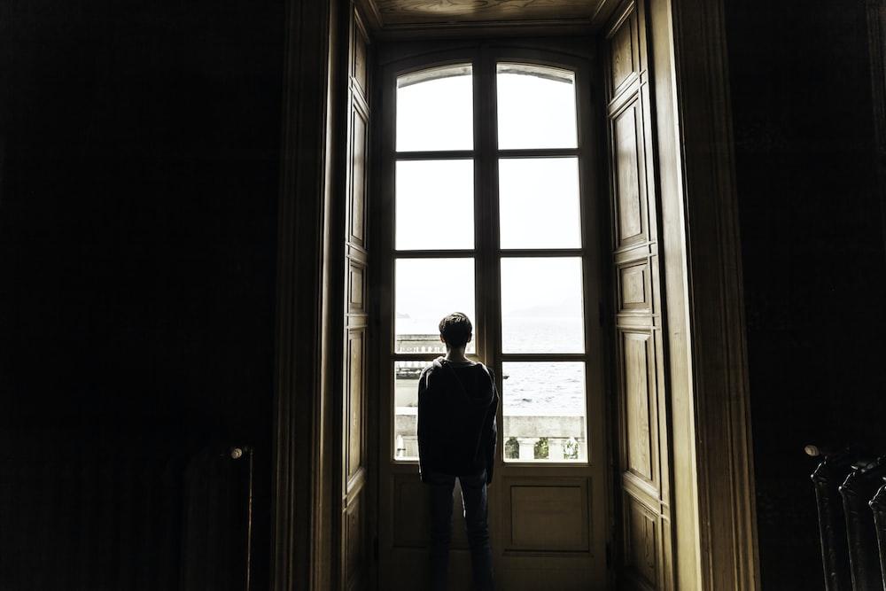 man standing near window panel