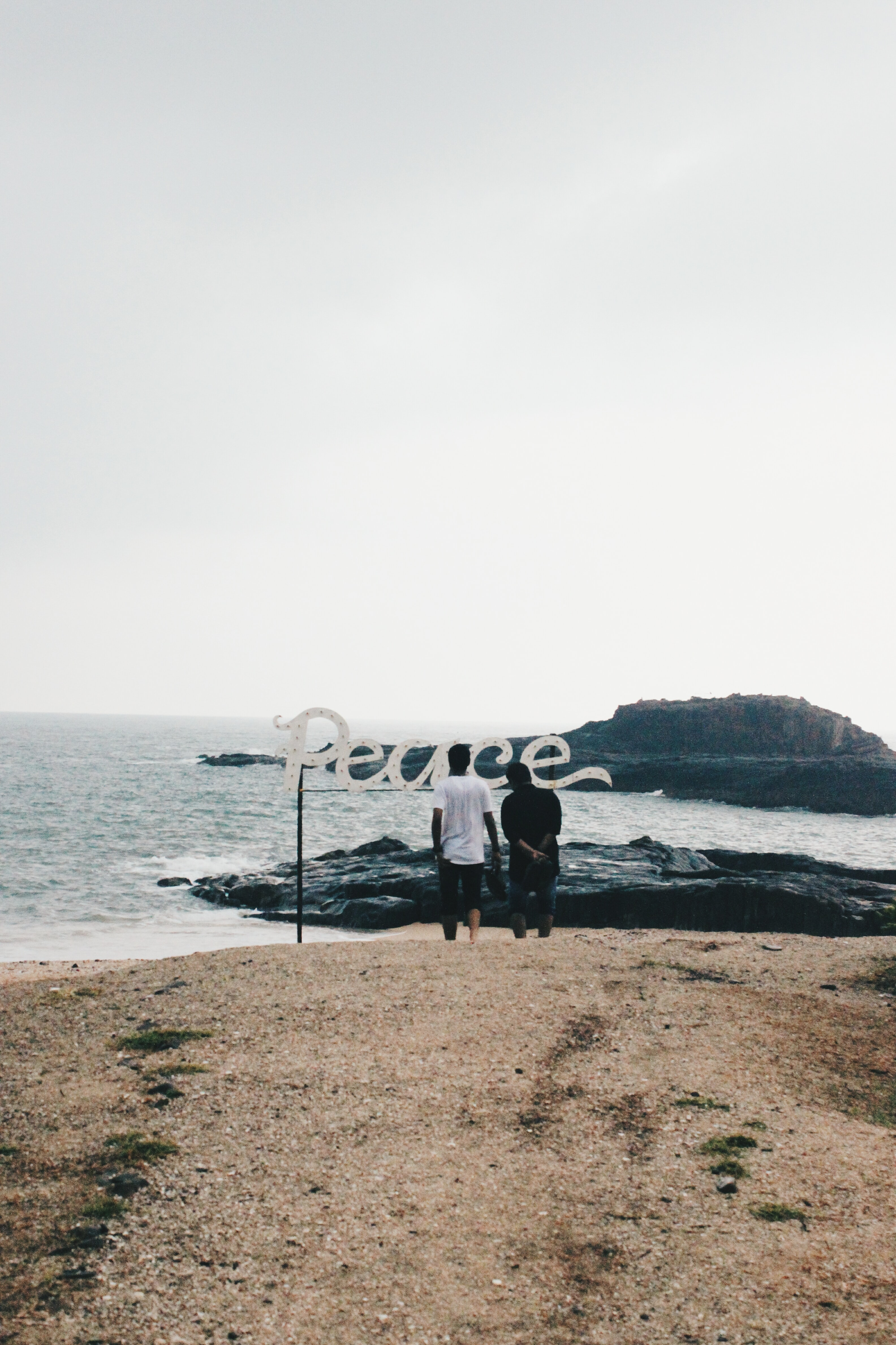 two persons standing on seashore