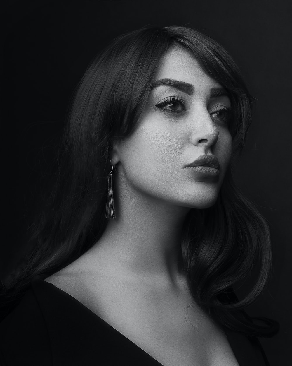 grayscale photo of woman wearing black top in black background
