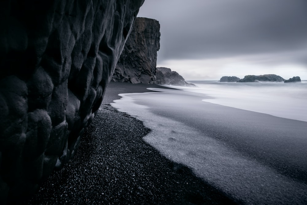 grayscale photography of seashore and calm sea