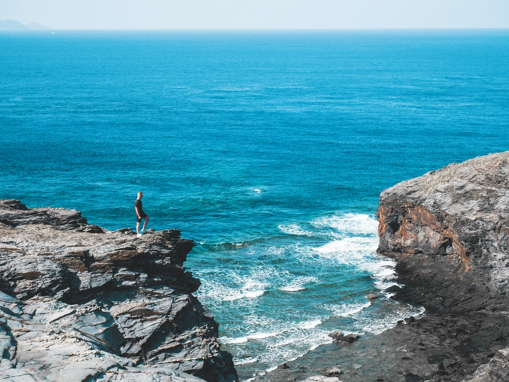 man standing on a rocky coast during daytime