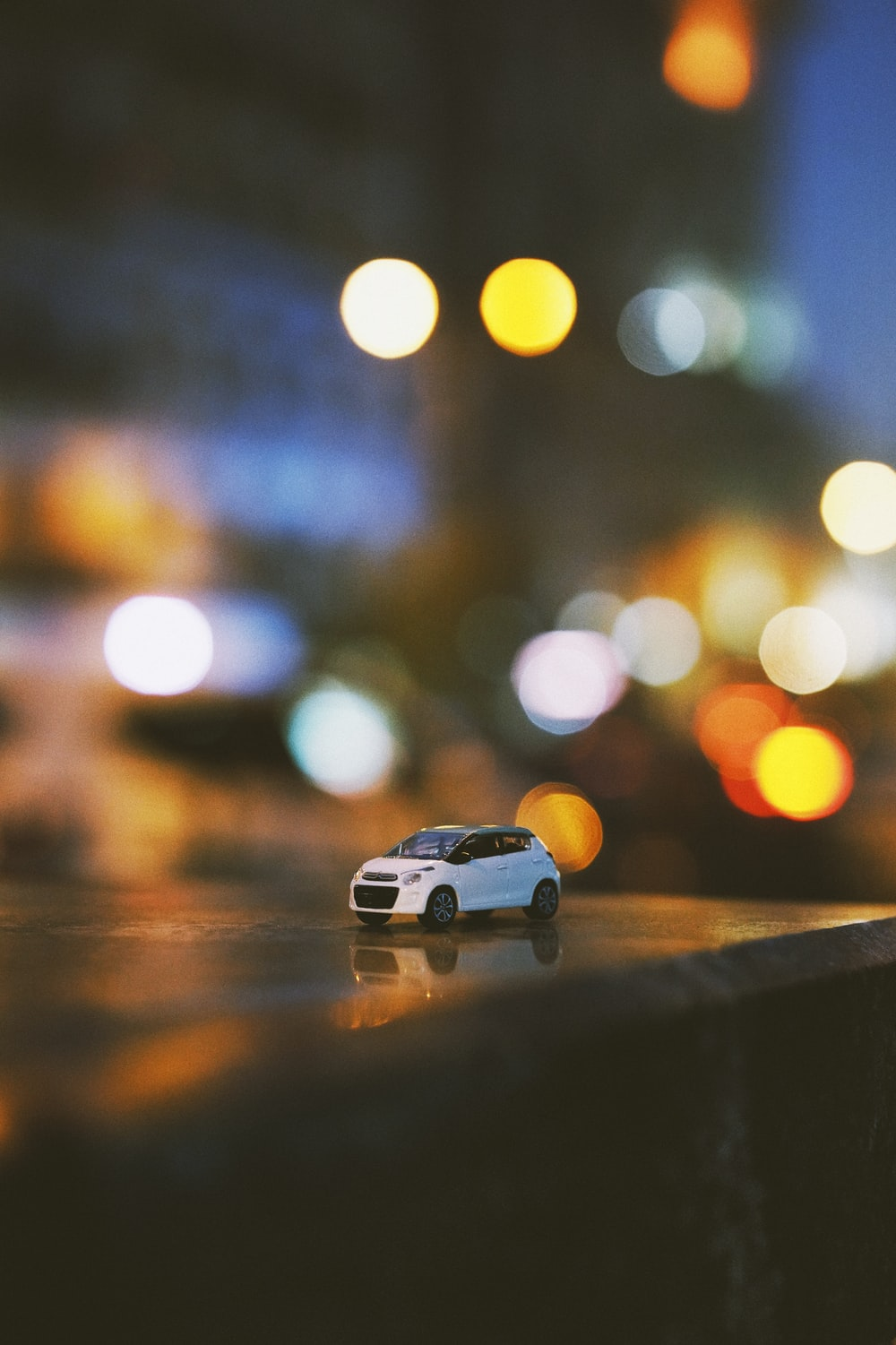 bokeh photography of white car miniature