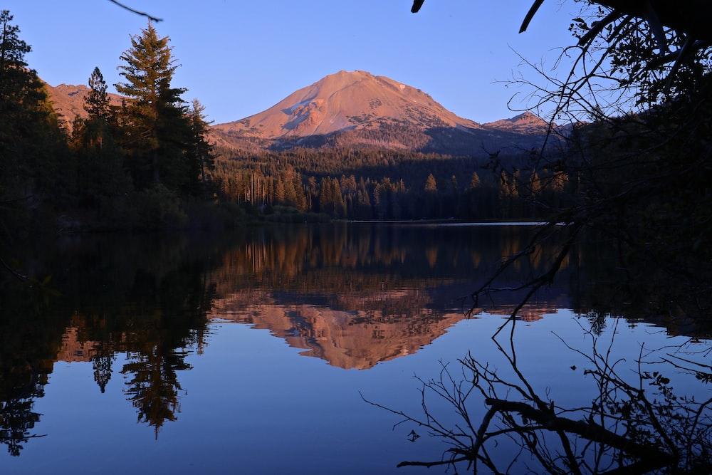 lake near mountain hill under blue sky