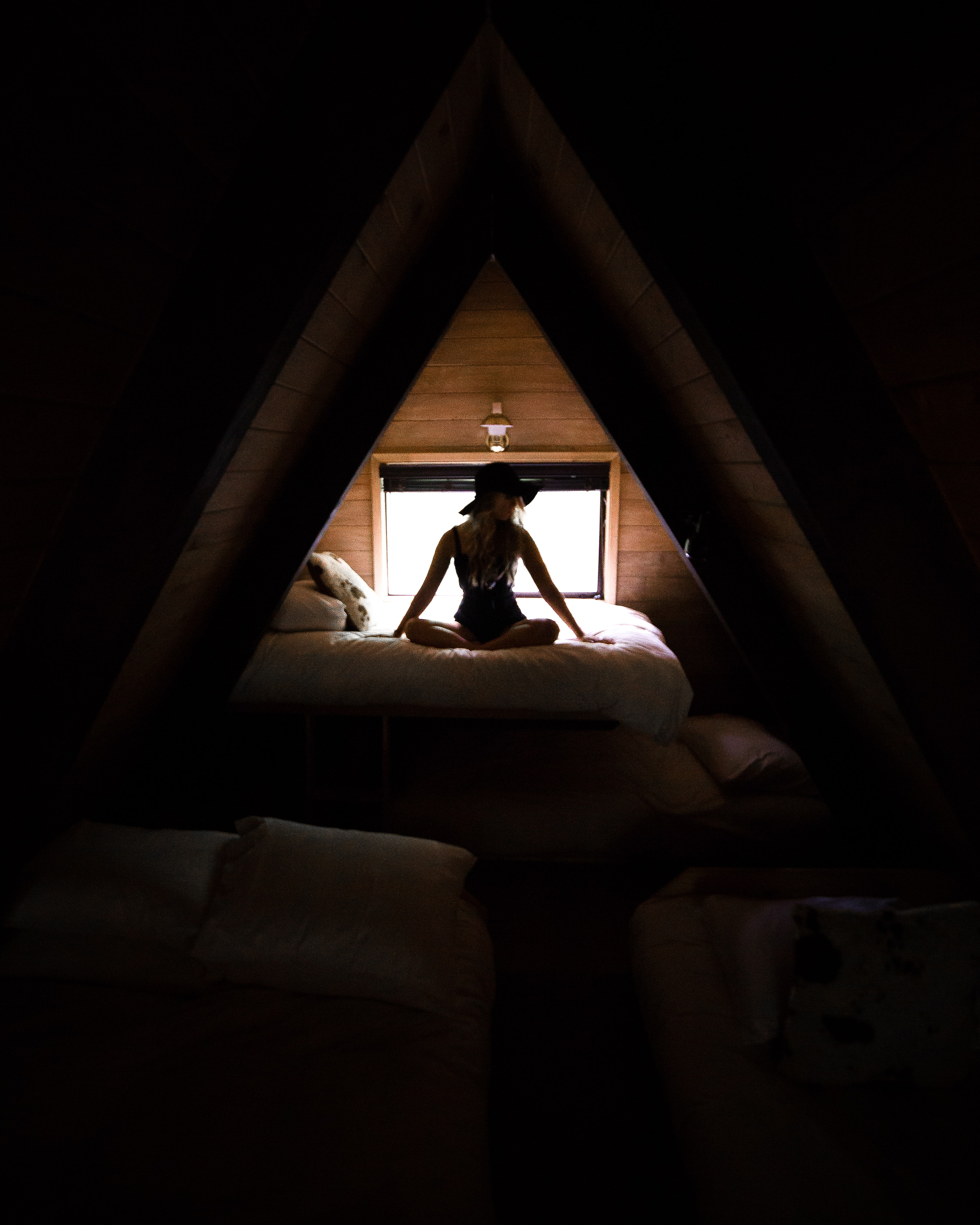 silhouette photography of woman sitting on bed