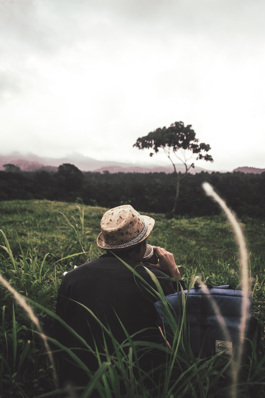 man sitting on green grass beside bag under nimbus clouds