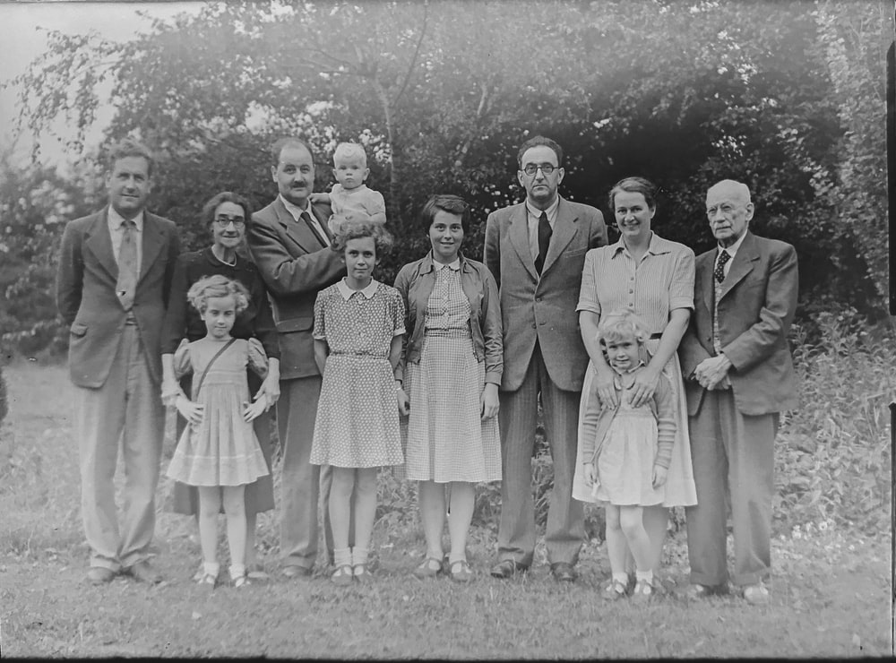 grayscale photo of family standing near trees